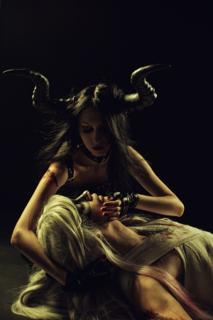 defeated: Seductive horned girl  holding head of fallen angel  Black  Stock Photo