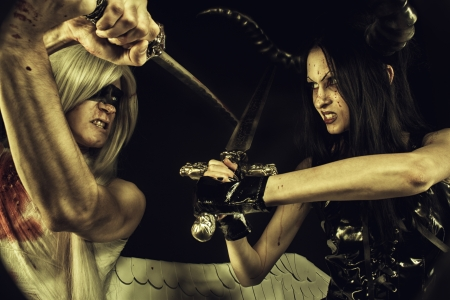 Wounded angel dueling with seductive horned demon