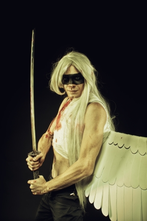 Strong young man with artificial wing and katana over dark  photo