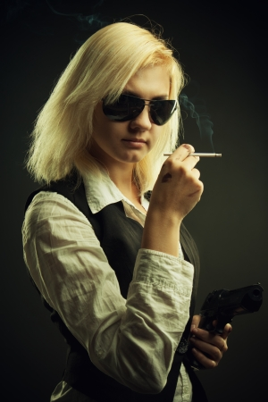 Girl in sunglasses with cigarette and pistol over dark background photo