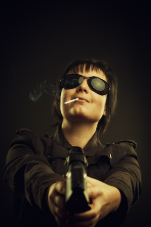 Funny girl with cigarette and gun over dark background photo