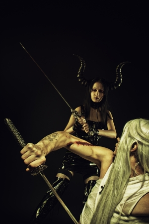 dueling: Wounded angel dueling with seductive horned demon