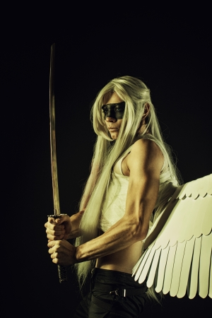 Strong mighty angel with katana posing over dark background photo