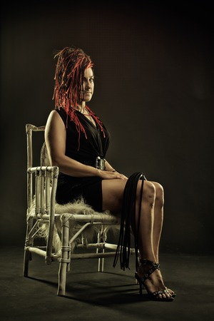 Mistress with lash sitting on a chair photo