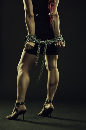 Chained girl posing over dark background photo