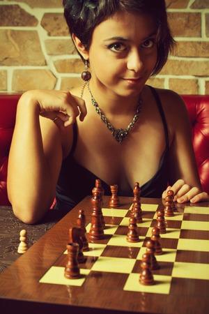 romance strategies: Seductive glamour girl playing chess Stock Photo