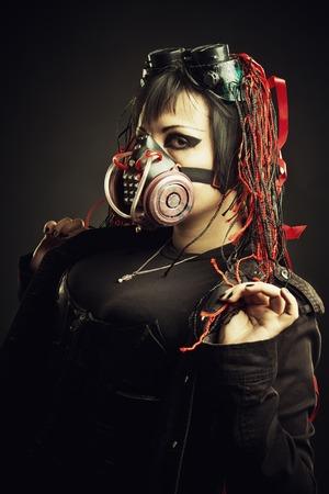 Girl in gas mask posing over dark background