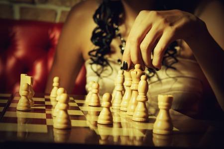 romance strategies: Glamour girl playing chess  Indoors shooting