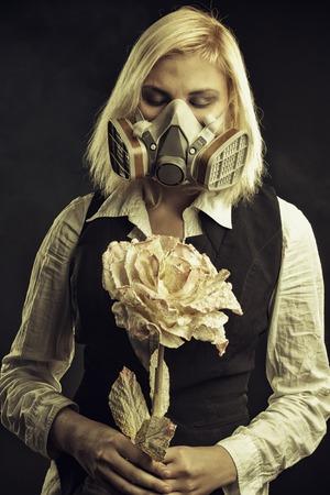 Pretty girl in gas mask holding flower over dark background Stock Photo