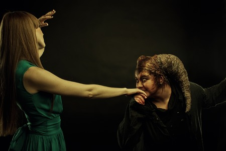 Sinister demon kissing woman's hand over dark background photo
