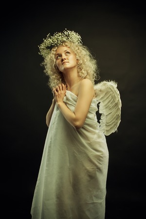 Pretty angel with wings posing over dark background photo