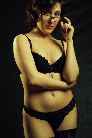 Sexy teacher in underwear posing over dark background photo