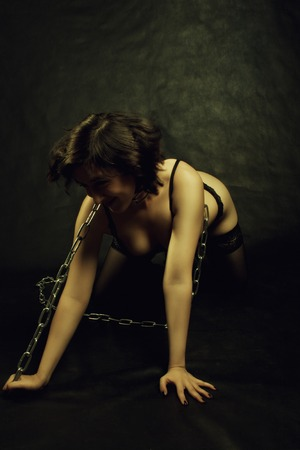 Chained funny sexy girl in underwear posing over dark background photo