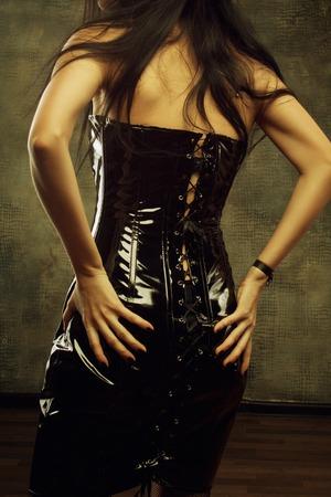 Seductive lady in latex dress  Rear view  photo