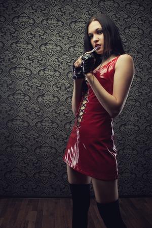 Sexy gothic girl in Latex roten Kleid, in leeren dunklen Raum Standard-Bild