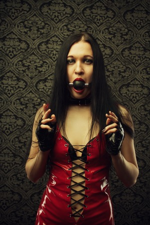 masochism: Pretty girl in red latex dress with mouth gag stands in an empty room  Stock Photo