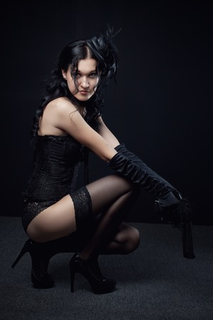 Seductive beautiful girl posing with gun over dark background photo