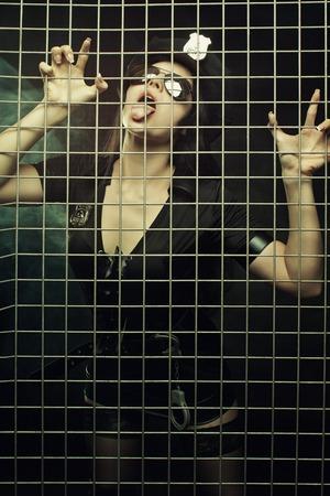 Seductive brunette girl in uniform posing behind bars photo