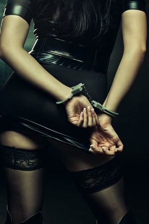 Seductive woman in handcuffs posing over dark background