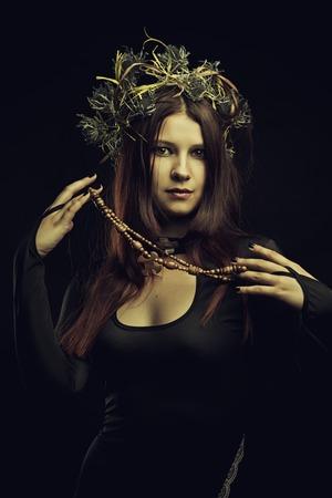 predictor: Pretty shaman woman in wreath over dark background