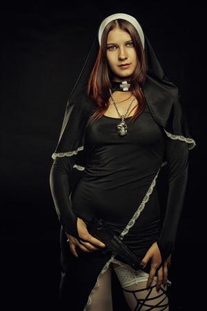 Seductive nun with gun posing over dark background photo