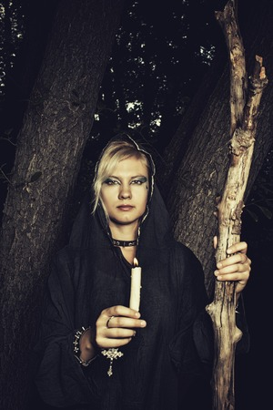 predictor: Young woman in hood with candle standing in the forest