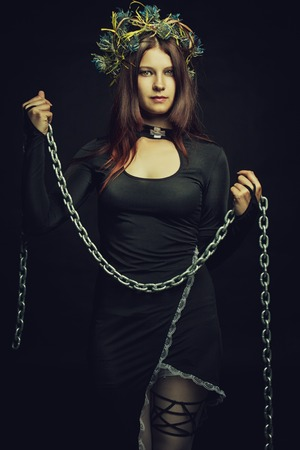 predictor: Seductive nun posing with chains over dark background Stock Photo