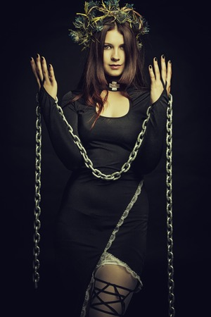 forecaster: Seductive shaman posing with chains over dark background
