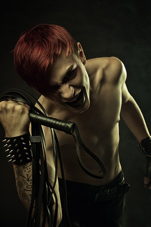 jailer: Redhead angry gothic man with lash over dark background