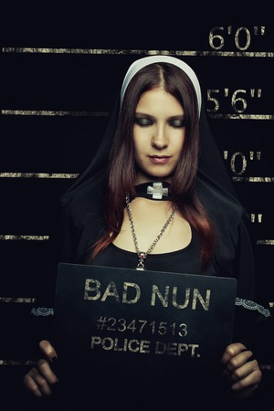 Mugshot of seductive girl in nun costume Stock Photo