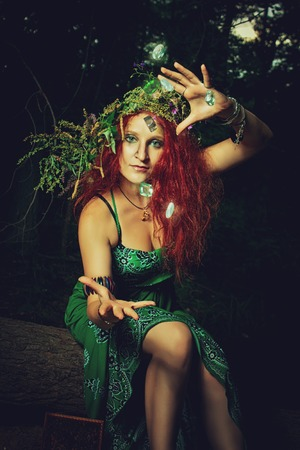 Redhead witch casting a spell in the forest Stock Photo