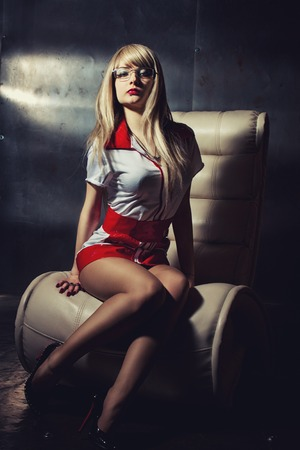 sexy female doctor: Seducutive nurse in sexy dress sitting on an armchair