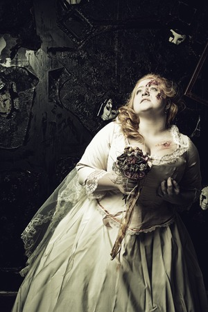 massacre: Wounded pale bride in old-fashioned vintage dress with faded flowers over grunged background