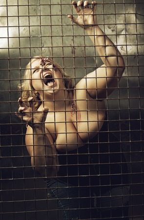Wounded woman screaming in a prison cell Stock Photo