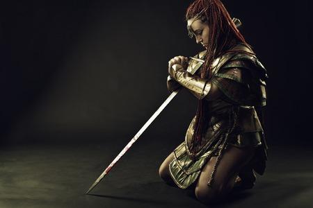 espadas medievales: Chica en la armadura de pie sobre sus rodillas con la espada Foto de archivo