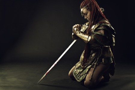 warrior girl: Girl in armor standing on her knees  with sword