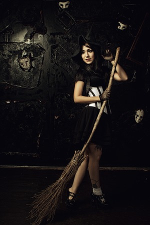 Seductive witch with broom posing over dark background Stock Photo