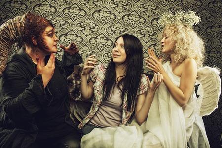 obedecer: Demon, �ngel y casual ni�a sentada en un sof� Foto de archivo