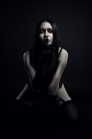 naked girl black hair: Sexy gothic girl standing on her knees over dark background Stock Photo