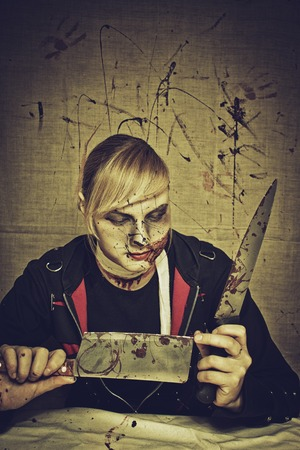 gory: Sinister maniac with two knives over bloody background