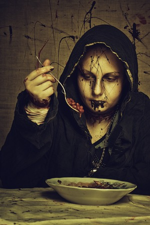 doomed: Young female cultist sitting in dirty room and having a breakfast Stock Photo