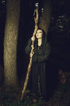 predictor: Girl in hood with staff in the forest Stock Photo
