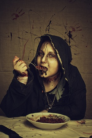 Bloody young girl in hood having a breakfast