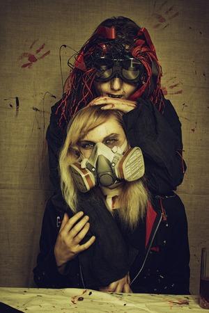 mascara de gas: Dos niñas cyberpunk posando sobre fondo sangriento