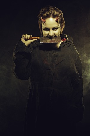 horned: Horned pale girl with bloody butcher knife over dark background Stock Photo