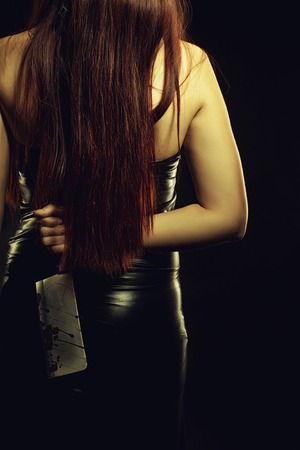 slasher: Seductive lady in latex posing with buther knife over dark background