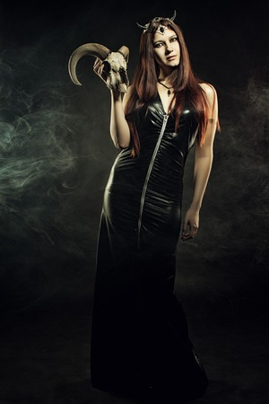 Sexy mistress in latex posing over dark background with skull photo