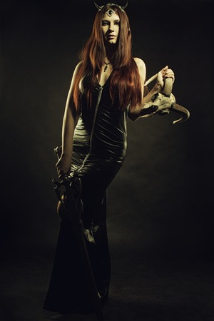 latex girl: Seductive girl in latex dress posing over dark background with skull and sword