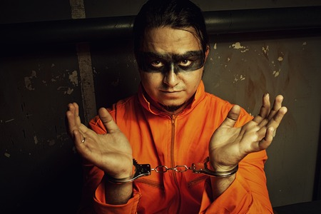wicked problem: Handcuffed prisoner in orange clothes in his cell