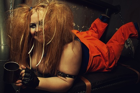 imprisoned: Funny prisoner in orange clothes laying on a bed in her cell Stock Photo